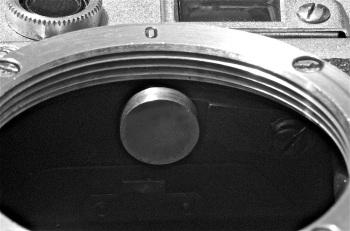 """foto 10: dettaglio interno del corpo macchina privo dell' obiettivo. In evidenza il cilindretto che,                mosso dall' obiettivo, aziona il telemetro. L' innesto a vite è standardizzato come indicato                  dallo """"O"""" presente sul bocchettone portaottiche."""